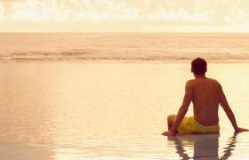 Travel Associates man sitting on infinity pool at dusk rarotonga